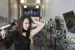 Asian hair stylist blow drying hair Stock Photos