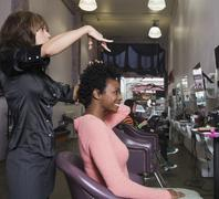 Hispanic hair stylist cutting African woman's hair - stock photo