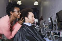 African hair stylist styling Mixed Race man's hair - stock photo