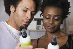 Multi-ethnic couple looking at hair product Stock Photos