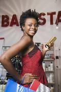 African woman holding shopping bag in salon Stock Photos