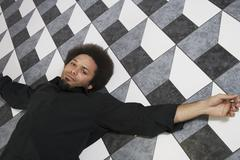 Mixed Race man laying on floor Stock Photos