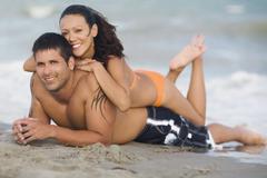 Hispanic couple laying on beach - stock photo