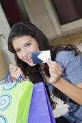 Hispanic woman holding credit card and shopping bags Stock Photos