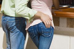 Stock Photo of Hispanic man's hand on girlfriend's hip