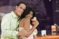 Hispanic couple hugging at bar Stock Photos