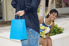 Hispanic man surprising girlfriend with gift - stock photo