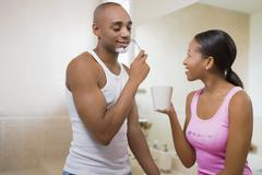 African woman watching husband shave - stock photo