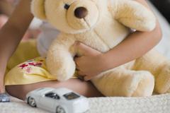 African girl holding teddy bear Stock Photos