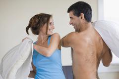 Hispanic couple having pillow fight Stock Photos