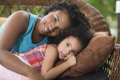 African mother and daughter laying on sofa Stock Photos