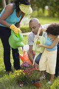 African family watering flowers Stock Photos