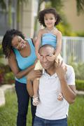 African mother watching daughter cover father's eyes Stock Photos