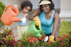 African mother and daughter watering flowers Stock Photos