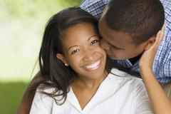 African man kissing wife's cheek Stock Photos