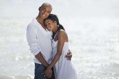 Stock Photo of Multi-ethnic couple hugging at beach