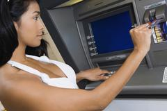 Hispanic woman using atm Stock Photos