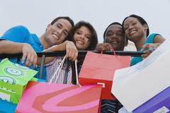 Multi-ethnic friends holding shopping bags Stock Photos