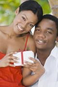Multi-ethnic couple holding gift Stock Photos