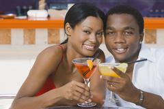 Multi-ethnic couple toasting with cocktails - stock photo