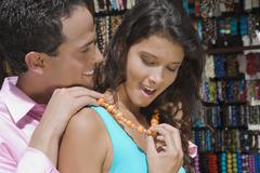 Hispanic man fastening necklace for girlfriend Stock Photos