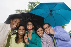 Hispanic businesspeople standing under umbrellas - stock photo
