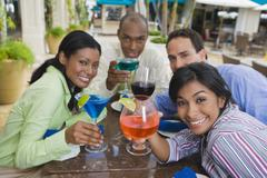 Hispanic couples toasting with cocktails Stock Photos