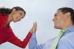Hispanic business people high-fiving Stock Photos