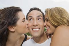 Hispanic women kissing man on cheeks Stock Photos