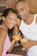 African couple holding orange juice Stock Photos