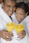 African couple toasting with orange juice Stock Photos