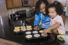 African mother and daughter making cupcakes Stock Photos