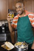 African man cooking and drinking wine Stock Photos