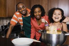 African parents watching daughter serve spaghetti - stock photo