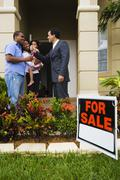 Hispanic real estate agent giving house keys to African family - stock photo