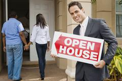 Hispanic real estate agent holding Open House sign Stock Photos