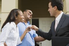Hispanic real estate agent handing house key to African couple Stock Photos