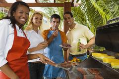 Multi-ethnic friends barbecuing Stock Photos