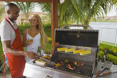 Multi-ethnic couple barbecuing Stock Photos