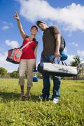 Stock Photo of Hispanic couple carrying camping supplies