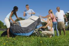 Multi-ethnic friends setting up tent Stock Photos