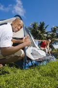 Multi-ethnic couple setting up tent Stock Photos