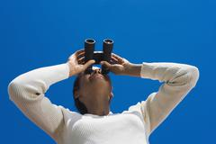 Hispanic woman looking through binoculars Stock Photos