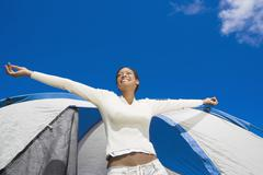 Hispanic woman stretching in front of tent Stock Photos
