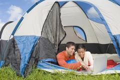 Hispanic couple looking at laptop in tent Stock Photos