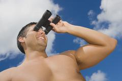 Hispanic man looking through binoculars Stock Photos