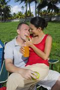 Hispanic woman feeding strawberry to boyfriend Stock Photos