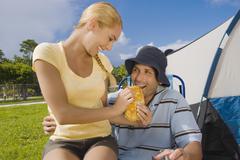 Hispanic woman feeding sandwich to boyfriend Stock Photos