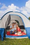 Hispanic family sitting in tent Stock Photos