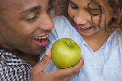 African father and daughter eating apple Stock Photos